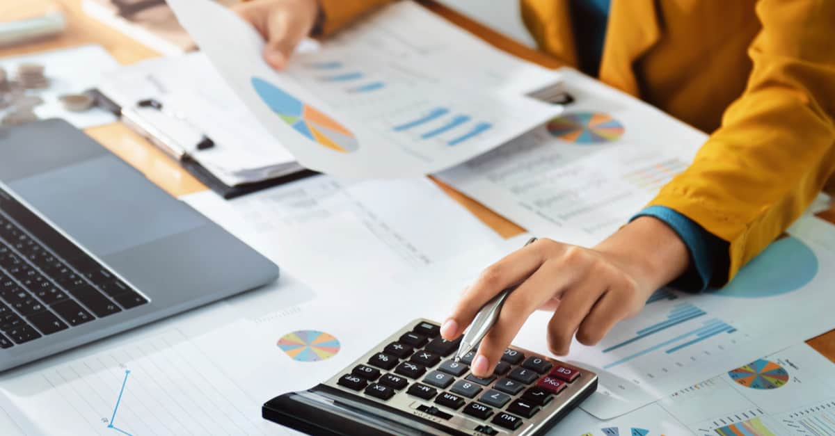 Finance Female accountant uses calculator and computer with pen turned on