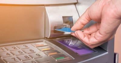 Mano insertando una tarjeta ATM en un banco para retirar dinero