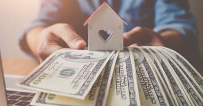 house wooden and banknote us dollar bills in hand ,Property investment and mortgage financial concept.