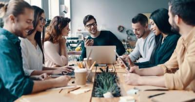 Equipo de marketing. Grupo de jóvenes modernos con ropa informal inteligente discutiendo algo mientras trabajan en la oficina creativa