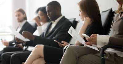 Candidatos multiétnicos sentados en la fila preparándose para la entrevista, candidatos de vacante negros y blancos esperando
