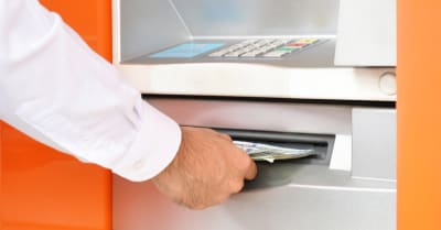 Hand taking (withdraw) money from ATM