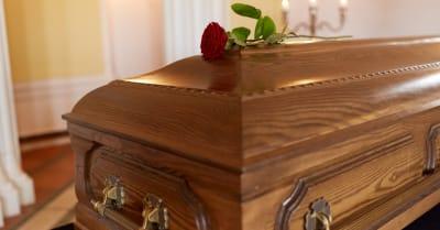 concepto funerario y de duelo - flor de rosa roja en ataúd de madera en la iglesia