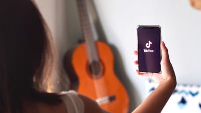 young-asian-woman-using-TikTok-application-on-iPhone-at-home