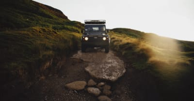 A Land Rover Defender off roading on a green lane in the North Yorkshire Moors in England