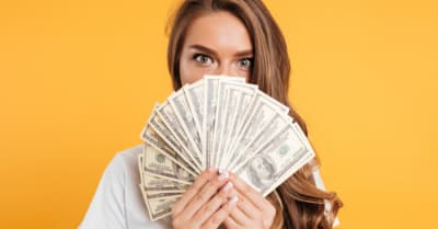 Close up portrait of a young girl covering her face with money banknotes isolated over yellow background