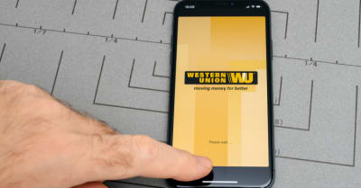 Male hand touch selecting New Apple iPhone x 10 smartphone after unboxing and testing by installing the Western Union money transfer app application software