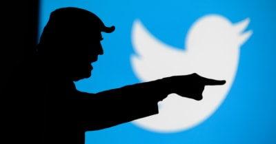 Donald Trump versus Twitter. Silhouette of angry American President in conflict with Chinese social network Twitter. Logo of company on blue screen in background