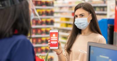 Mujer moderna con máscara en la cara usando cupón de descuento digital en su smartphone en el supermercado