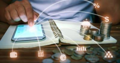Un hombre trabaja con una aplicación de calculadora de teléfonos inteligentes, filas de monedas en libros