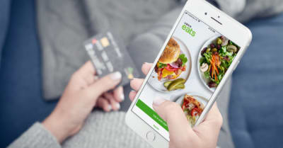 Woman using uber eats app on Apple iPhone 8 plus at home for order food delivery