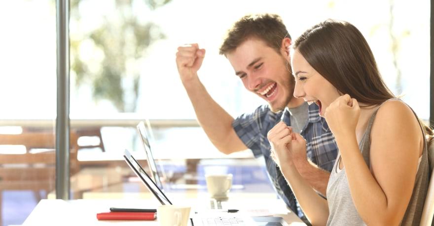 Grupo de dos jóvenes estudiantes eufóricos viendo los resultados de un examen en una laptop en una mesa de un bar universitario