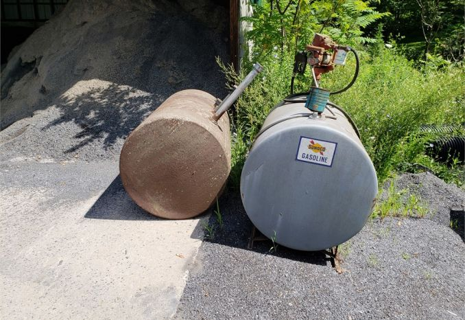 Pair of above ground fuel tanks, one with a pump