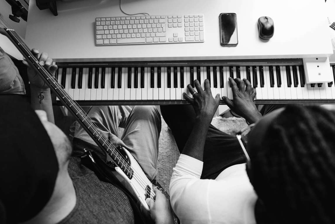 Two people sitting at desk with a macintosh and a piano underneath, being played, while a bass guitarist plays to the left.