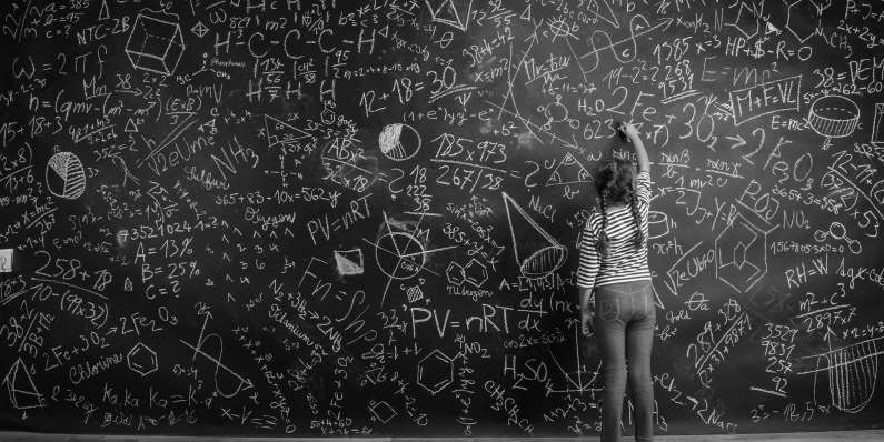 Girl writing equations on a completely filled chalkboard with mathematics found in engineering, algebra, and quantitative finance.