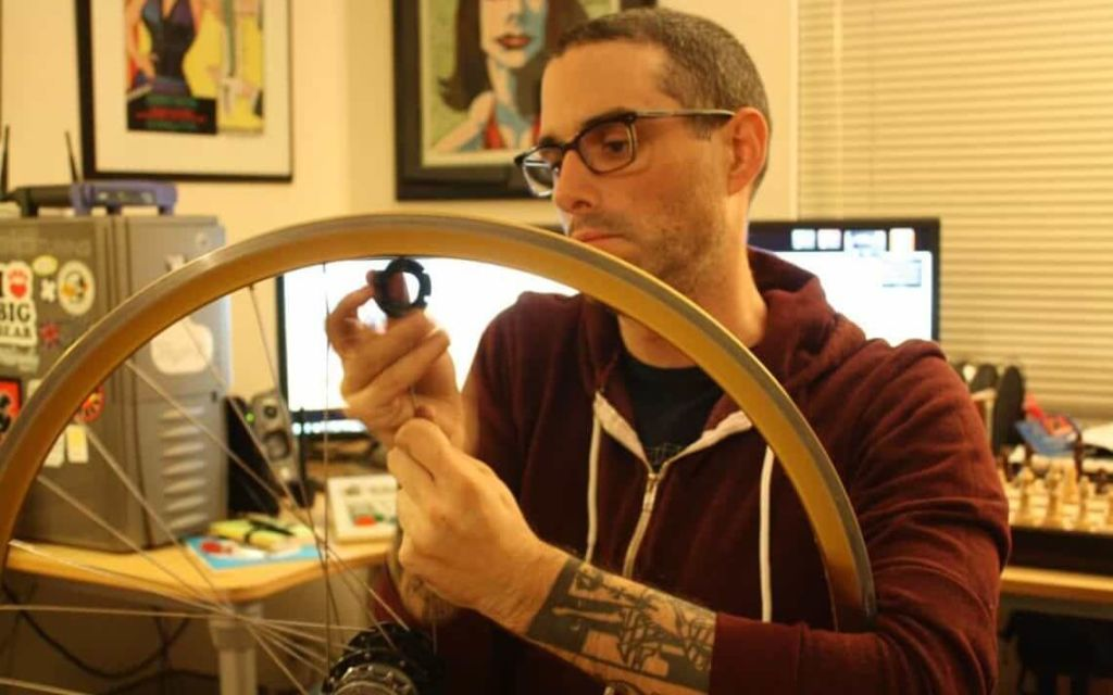 Josh_Sawyer_removing_spokes_from_a_bicycle_wheel.