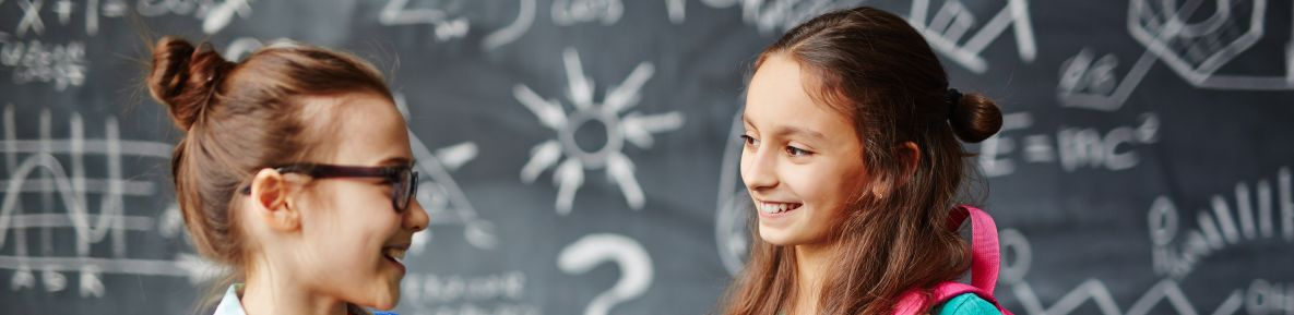 Two girls smiling at each other in front of a black board