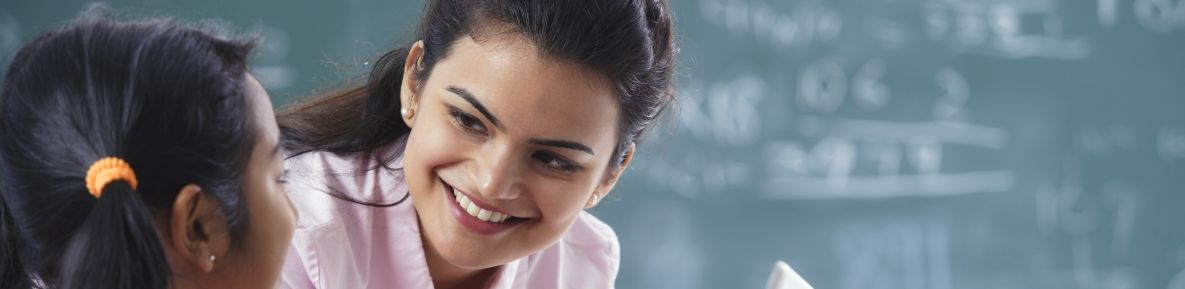 Student and a teacher smiling at each other