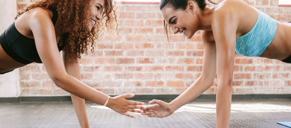 Two women in plank position smiling
