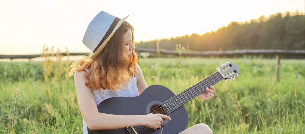 Girl playing a guitar in a field