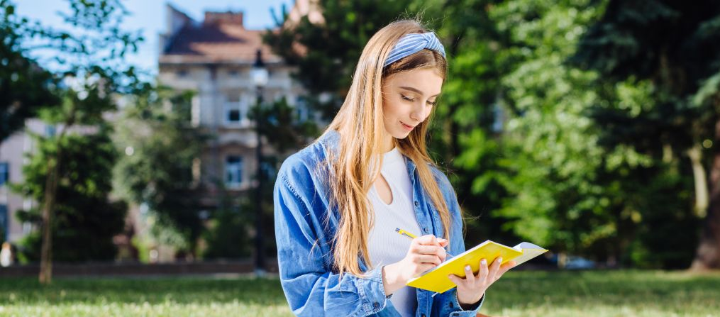 Girl sitting on grass and writing in notebook