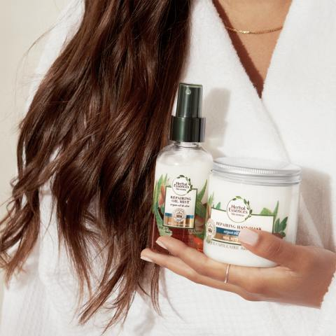 Female holding two Herbal Essences products: Argan oil and aloe hair oil and argan oil and aloe hair mask