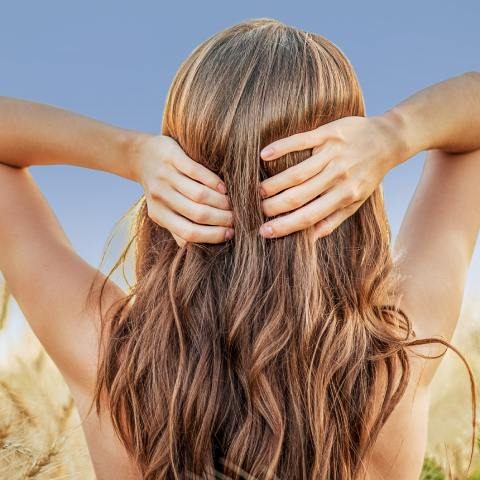 A woman shot from behind, with healthy, shiny hair
