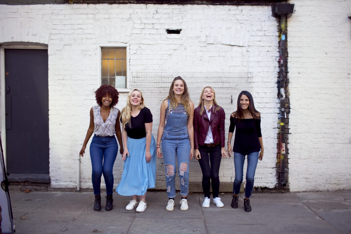 Girls standing in front of a white brick wall and laughing