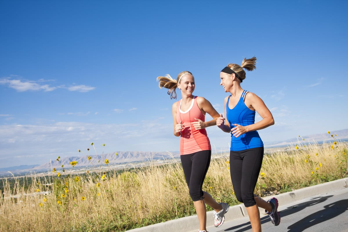 Two women running in nature and smiling at each other