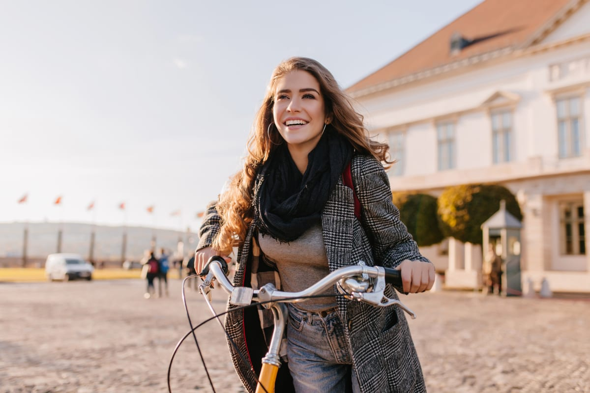 Woman holding her bike and smiling while looking at the distance
