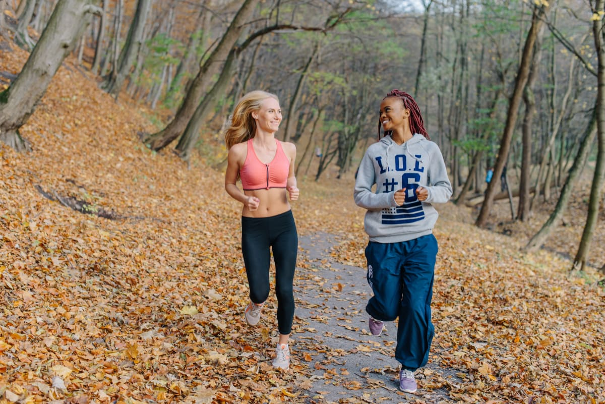 Two women running in the forest and smiling at each other