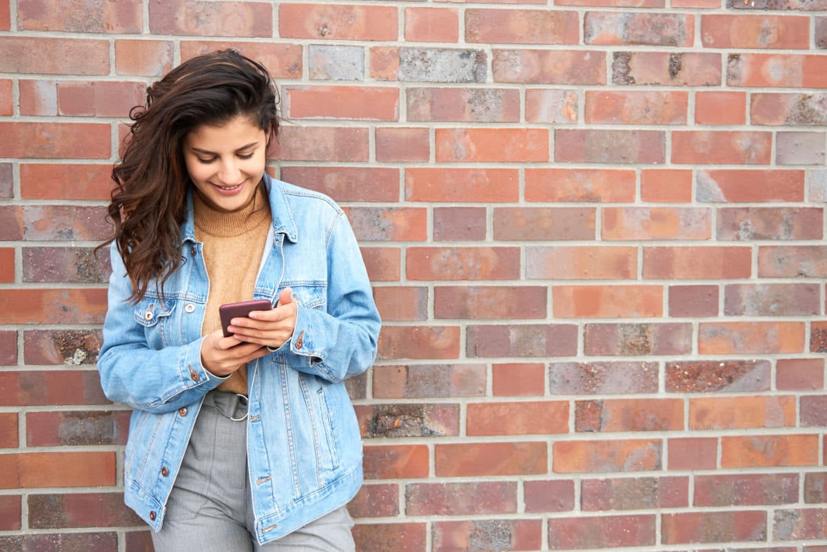 A girl in front of a brick wall looking at her phone