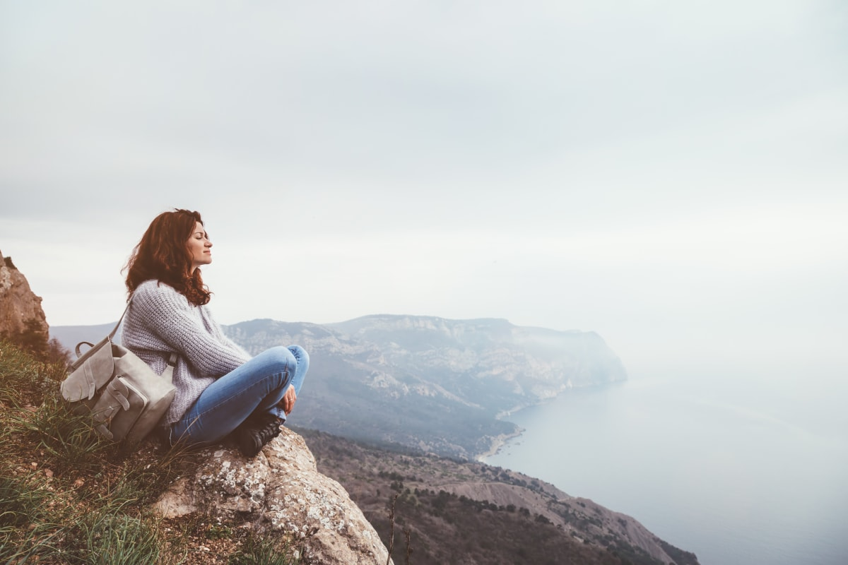 Woman sitting at the top of a rock and looking at the sea