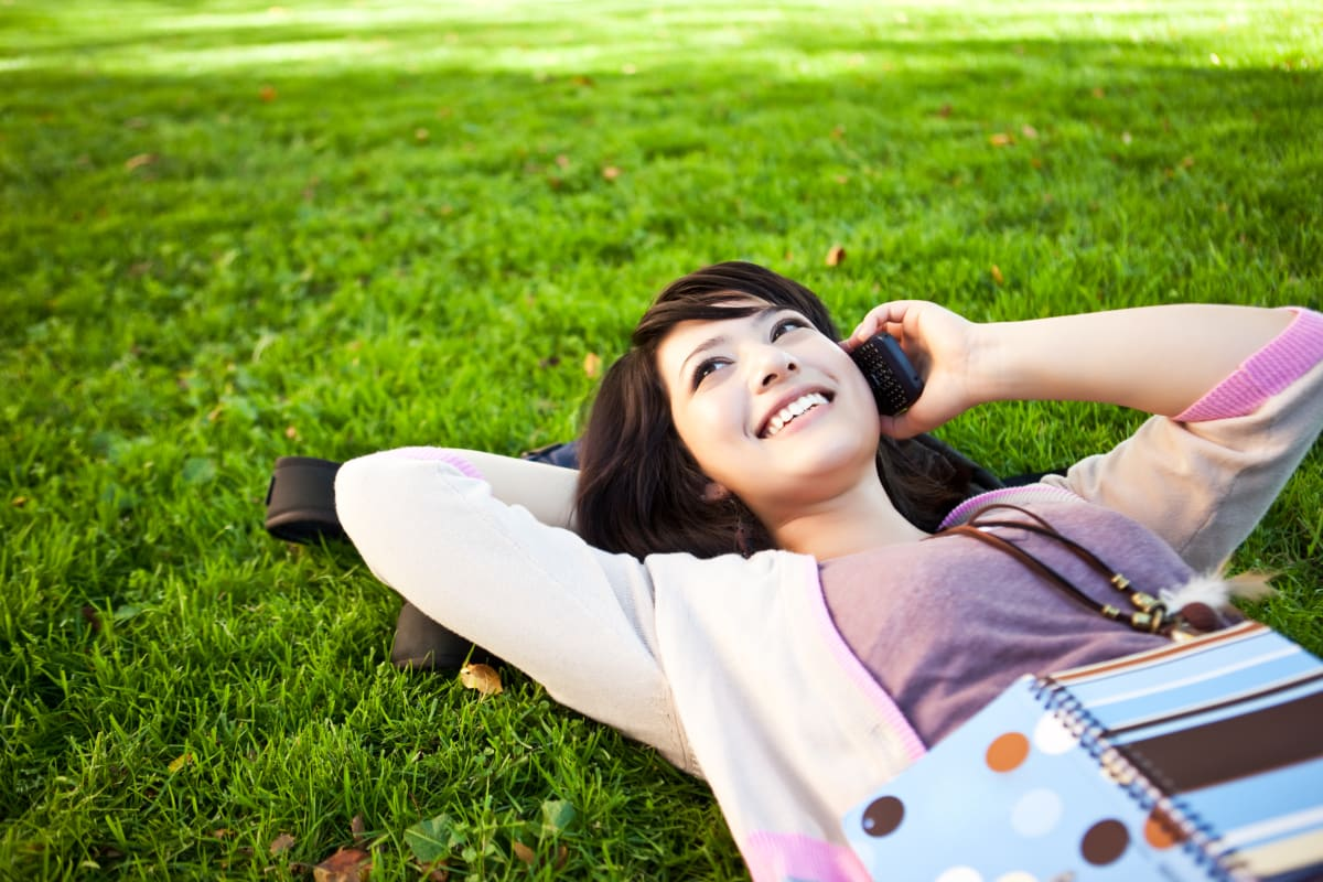 Woman lying on grass and talking on her phone