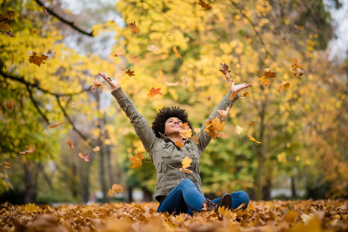 Woman sitting on the ground and throwing autumn leaves into the air