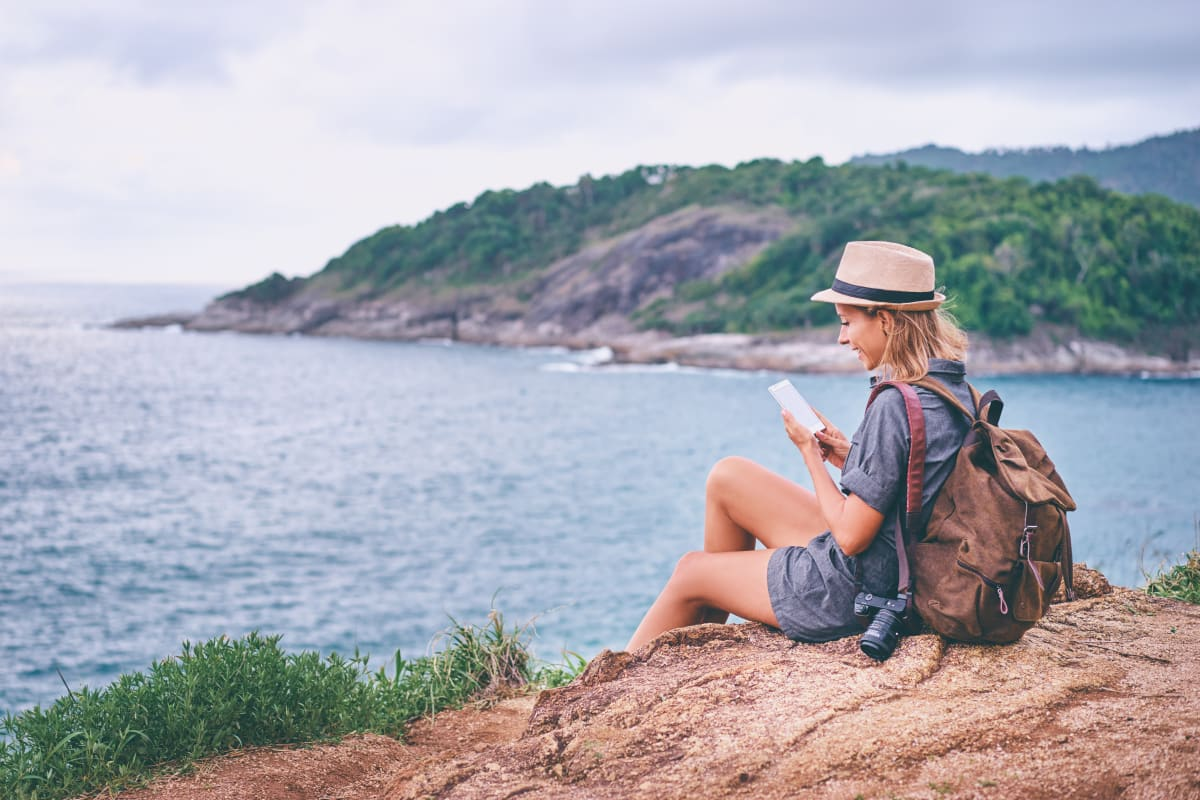 Woman sitting on a rock on the beach and reading a book