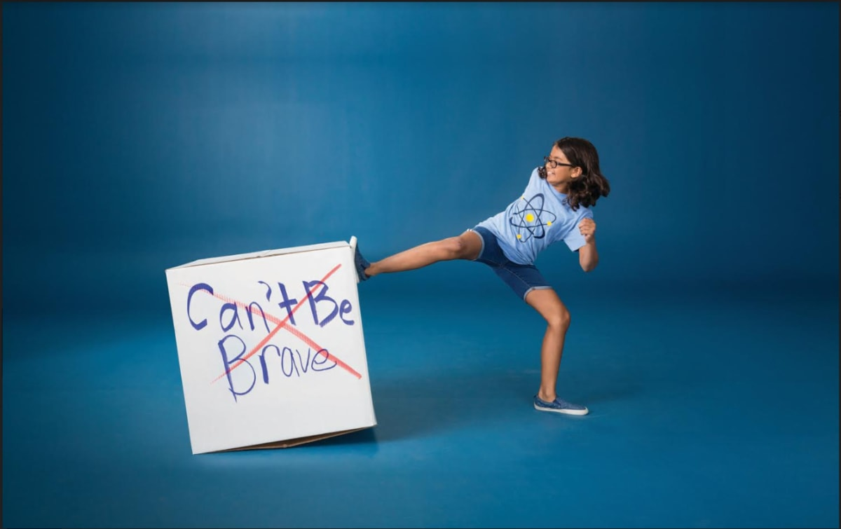 "Girl kicking a cardboard box that has ""Can't be brave"" written on it"