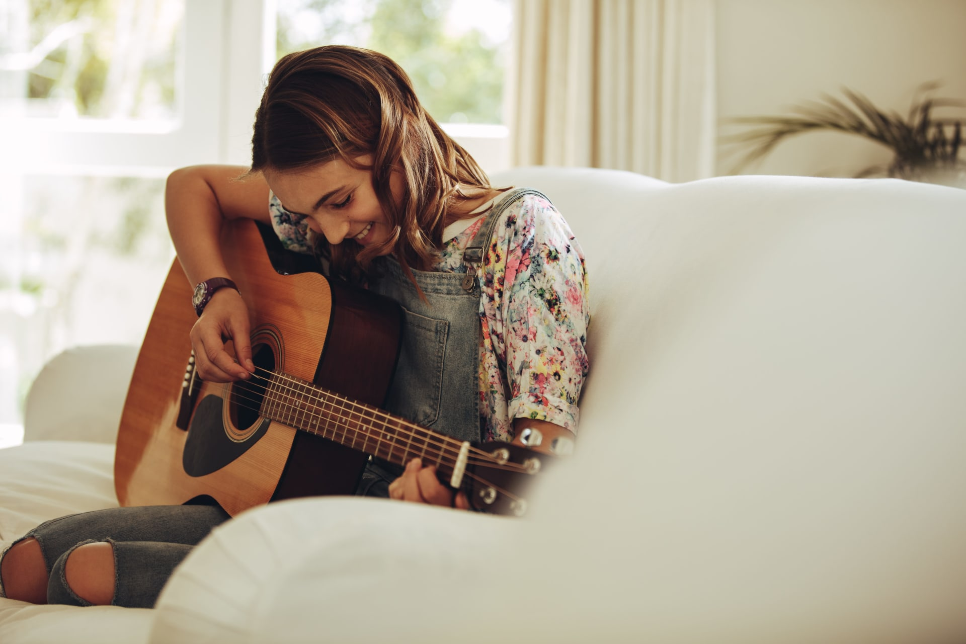 Happy young girl playing a guitar on the couch