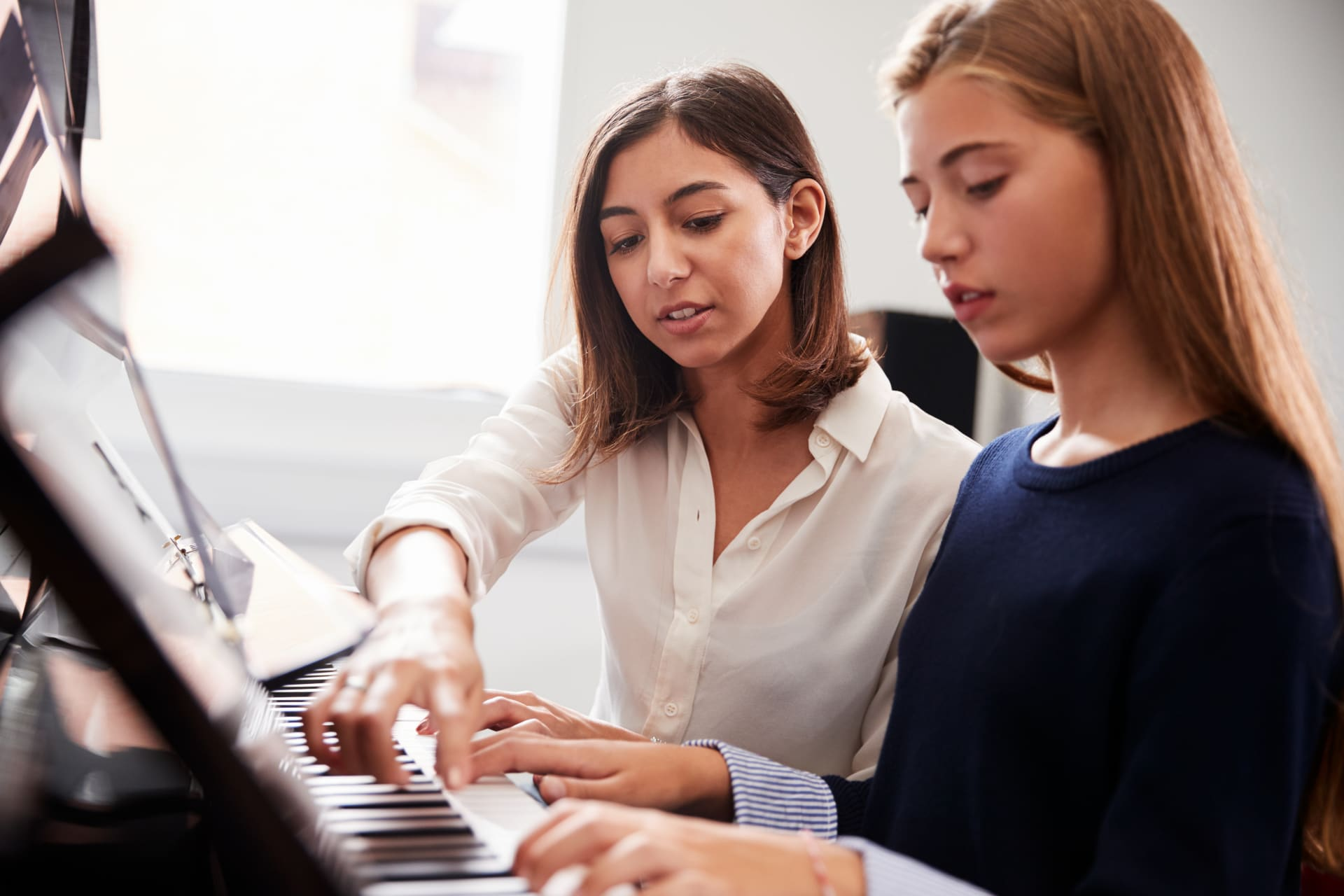A young girl with the piano teacher