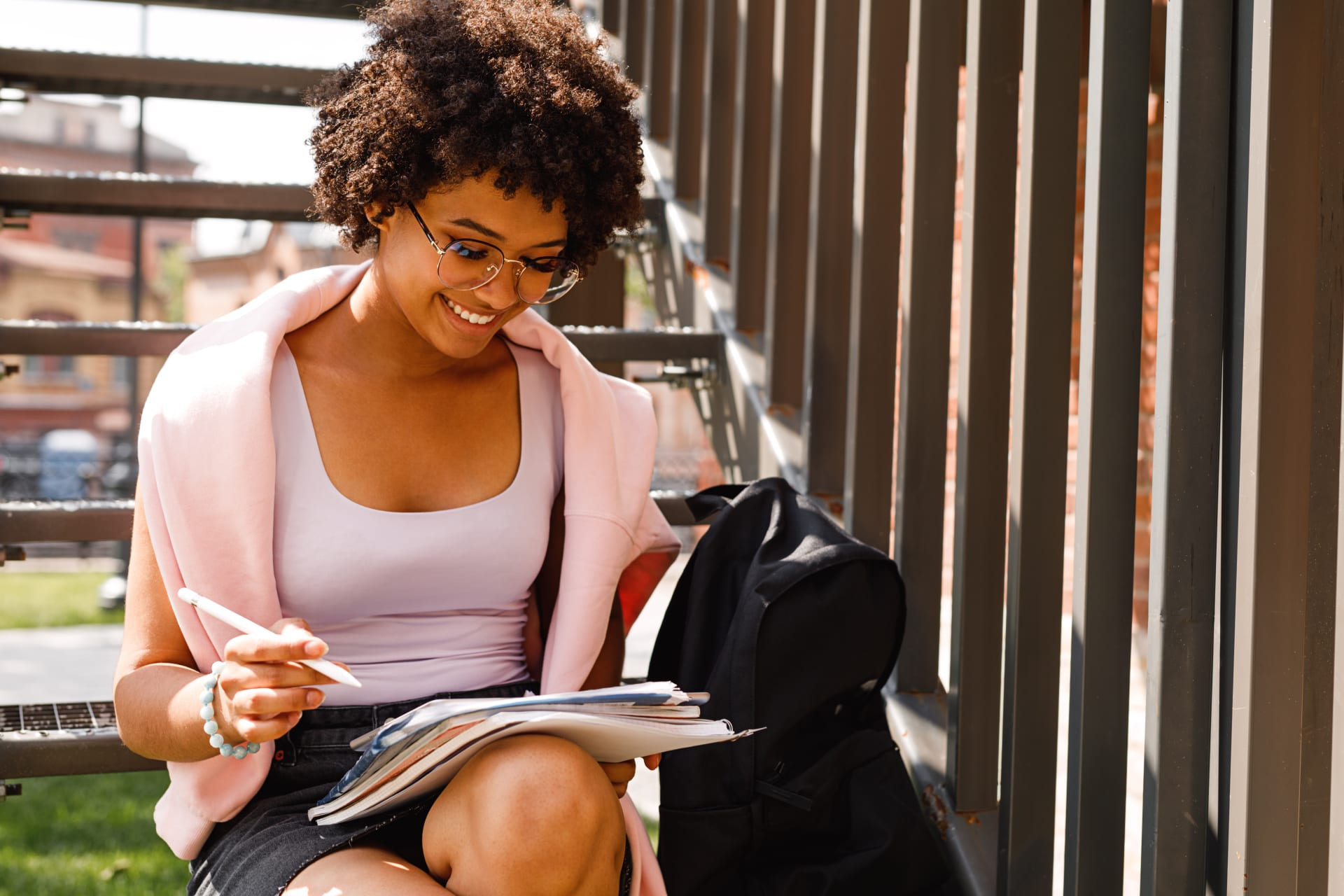 Girl smiling and sitting at the stairs while looking at her papers