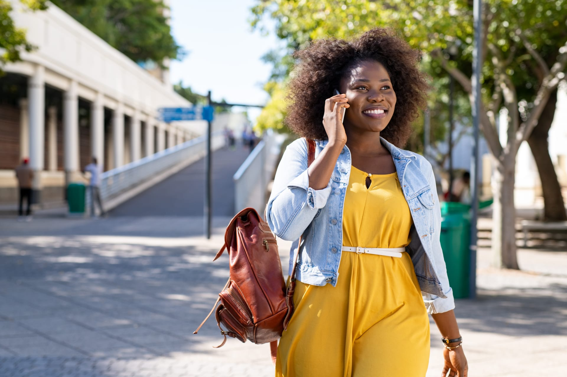 Woman smiling while talking on her phone and wallking down the street