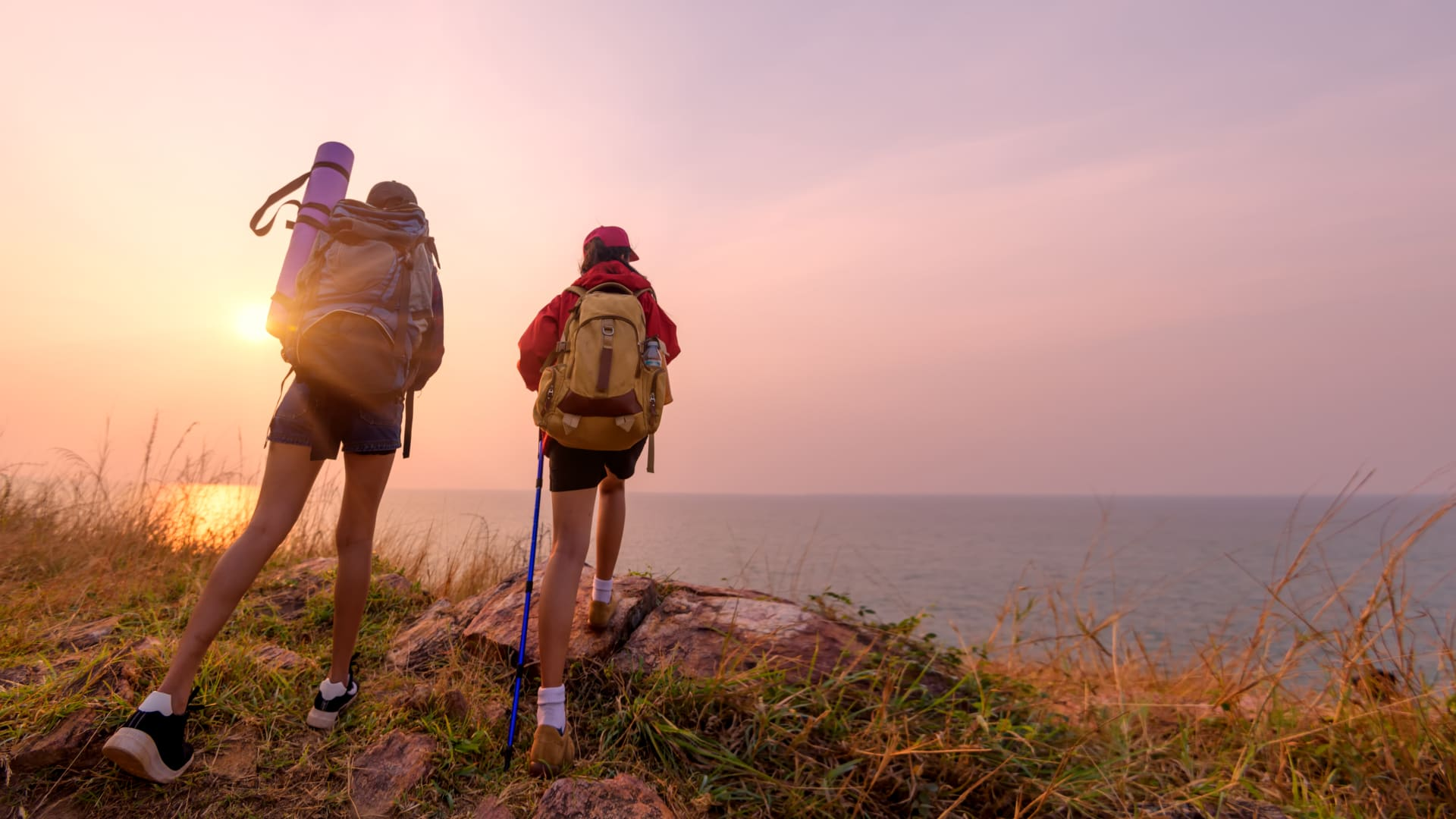 Two women hiking near the seashore whit sunset in the background