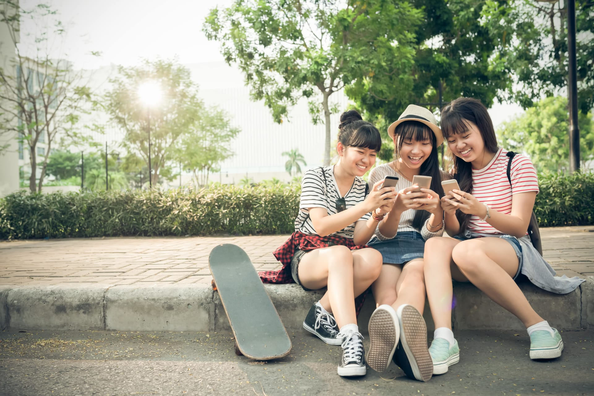 Three girls sitting on a sidewalk and looking at their phones