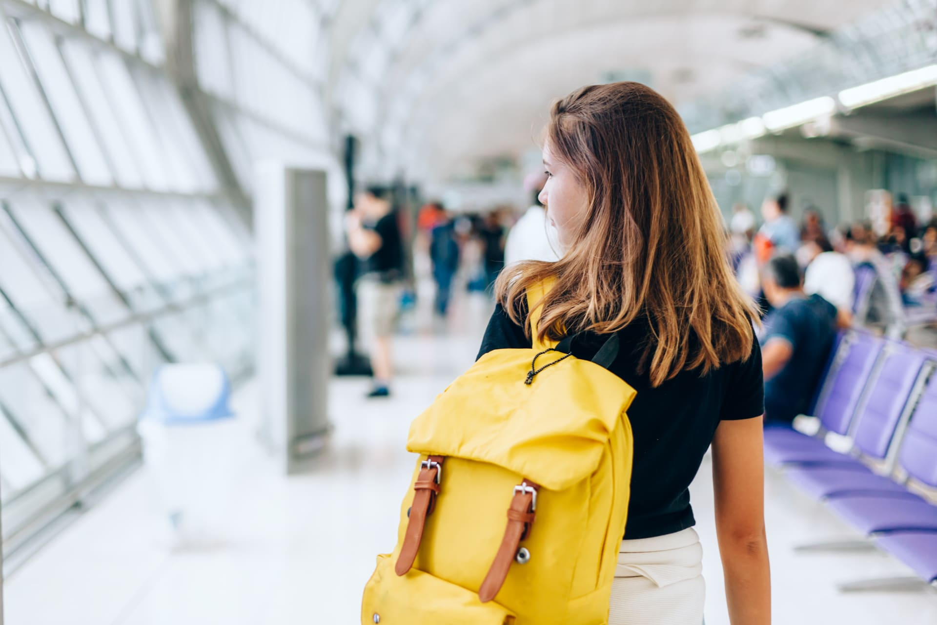 Rear photo of a girl wearing yellow backpack