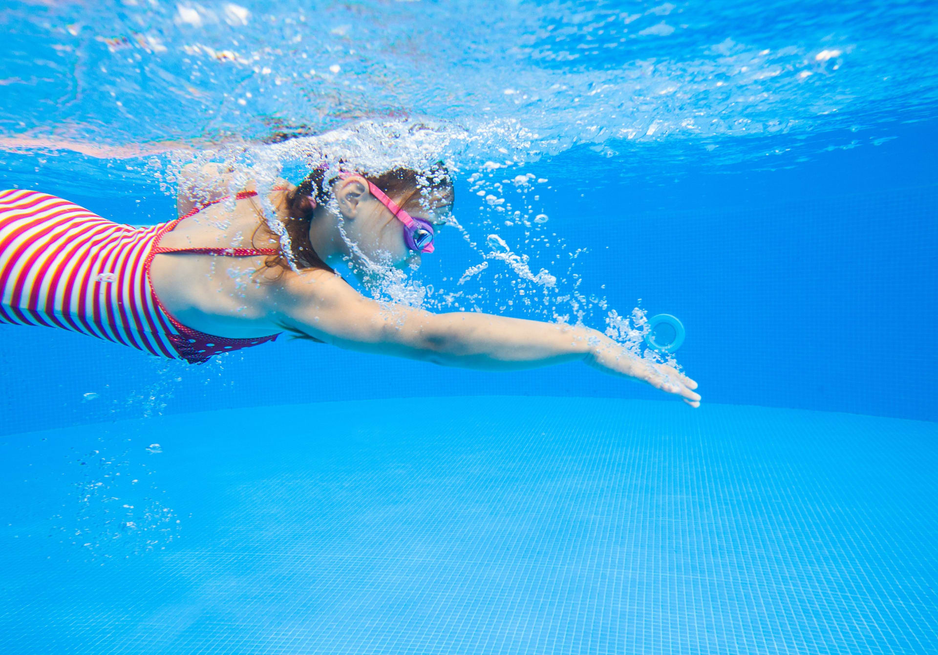 Underwater photo of a girl swimming in the pool