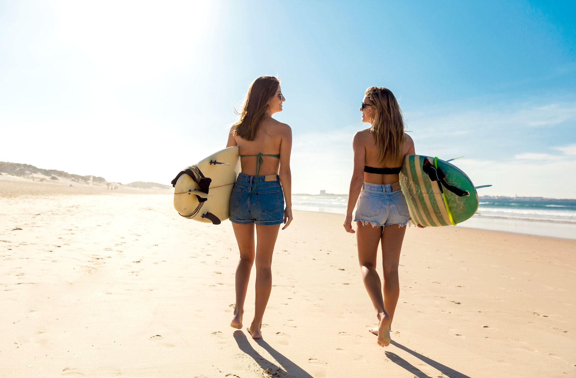 Two women walking on the beach and holding surf boards