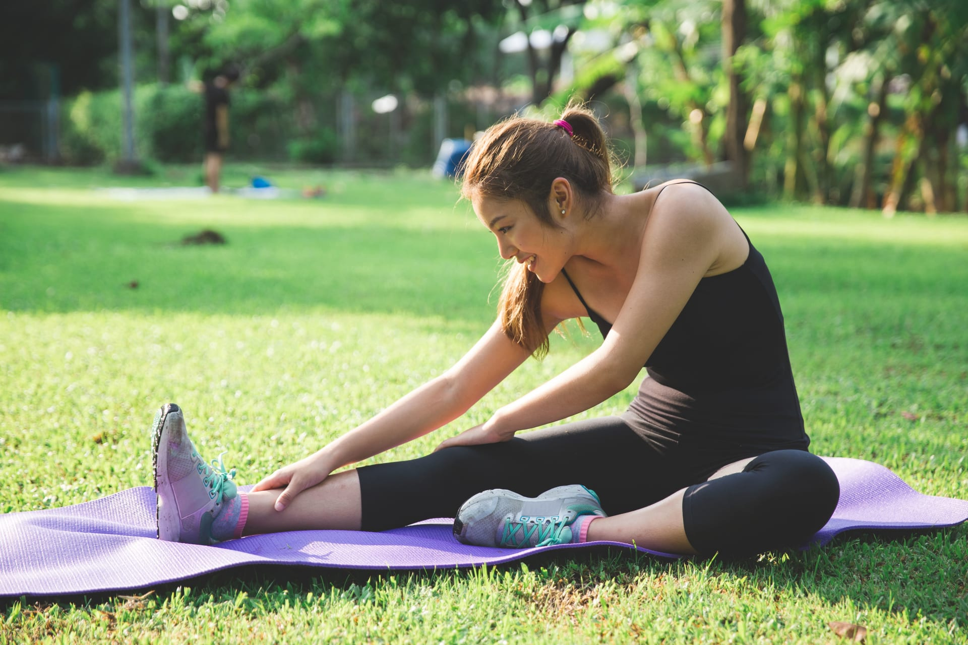 Girl stretching in nature on a yoga mat
