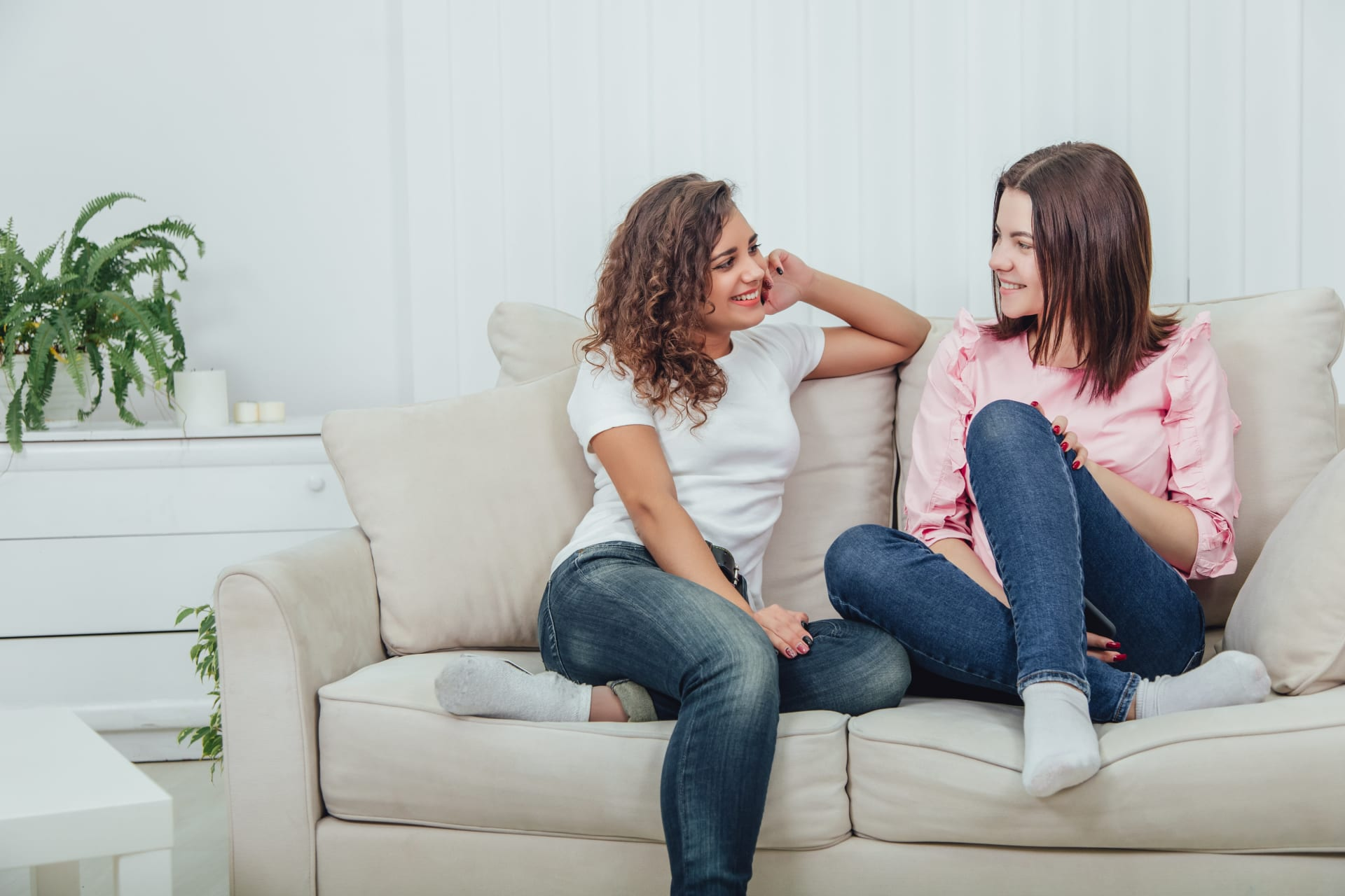 Two girls talking while sitting on a couch
