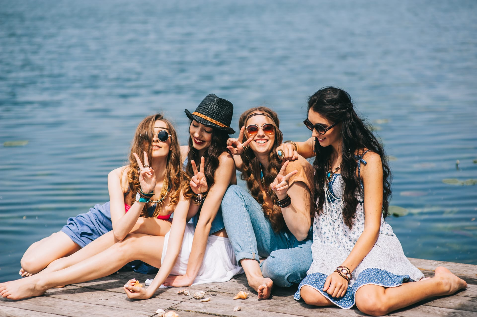 Four girl sitting on a dock and smiling