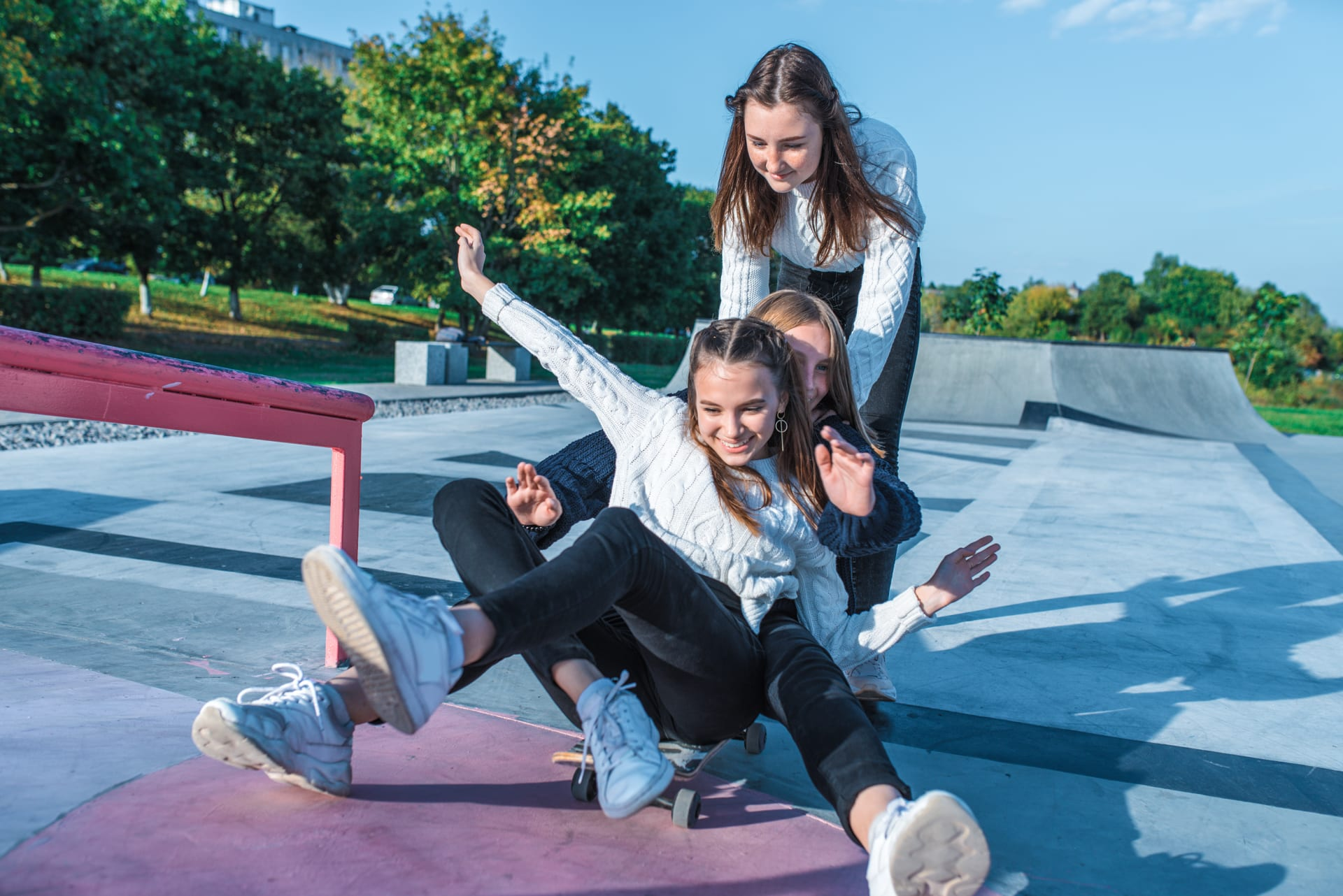 Girls playing and riding a skateboard